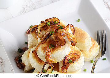 closeup top view pierogies with caramelized onions and a fork