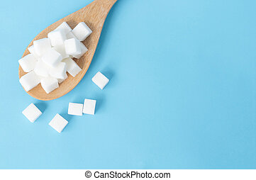 Closeup top view sugar cubes on wooden spoon white blue background