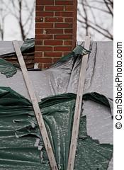 Closeup torn tarps chimney - Light snow falls on the torn...
