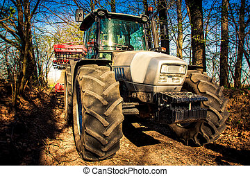 closeup tractor on soil road in spring forest