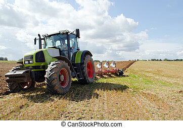 Closeup tractor plowing agricultural field autumn