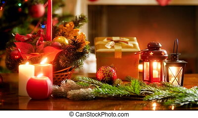 Closeup video of beautiful decorated christmas table with candles and gifts against glowing Christmas tree and burning fireplace