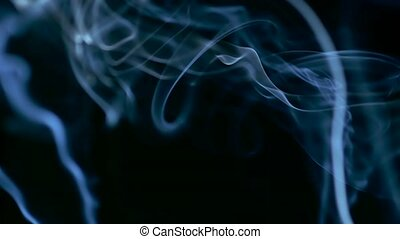 Closeup video of blue smoke rising over black background in...