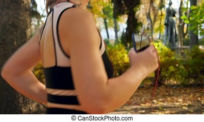 Closeup video of young sporty woman holding smartphone while...
