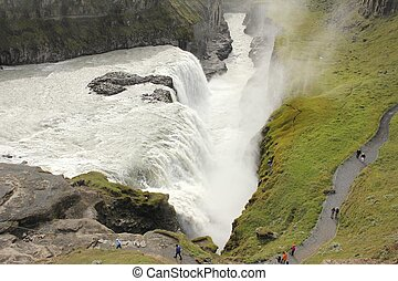 Closeup view from above on Iceland's Gulfoss waterfall with people watching the water falling into the canyon