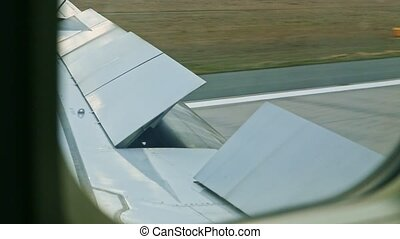 closeup view from aircraft window on open steel wing moves by empty runway