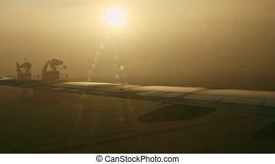 closeup view from airplane window on steel wings against bright sun through fog