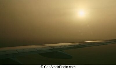 closeup view from window on airplane wings against bright sun through fog on sunrise