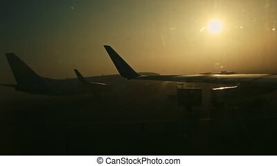 closeup view from window on plane wing against big aircraft silhouette on sunrise