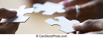 Closeup view hands of multiethnic people holding pieces of puzzle