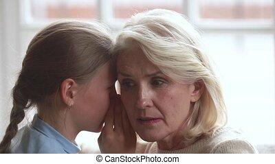 Closeup view little granddaughter whispering secret at ear...