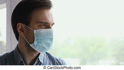 Close up view 35s man wears blue disposable medical face mask looking out the window. Corona virus covid-19 pandemic outbreak disease, caution preventive measures, stop covid-2019 quarantine concept