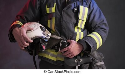 Close-up view of a brave firefighter in special uniform holds protective helmet standing against a gray wall