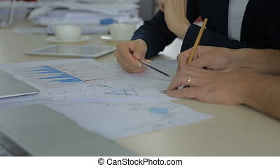 Closeup view of a colleagues financier, trader using a pencil to draw a line on a graph of securities trading. discussing data