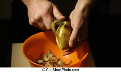 Closeup view of a male hand peeling an organic potato.