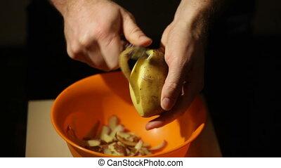 Closeup view of a male hand peeling an organic potato.