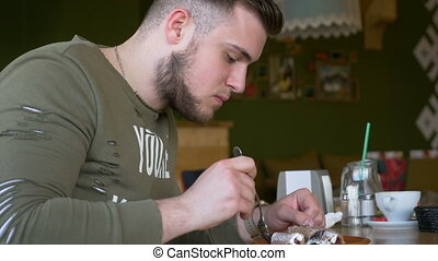 Closeup view of a young man with smartwatch eating delicious cake in a cafe