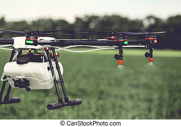 Closeup view of agriculture drone spraying water fertilizer on the green field