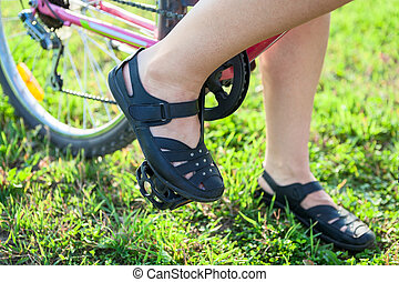 Closeup view of cyclist feet on pedals of bicycle