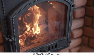 Closeup view of fireplace with burning wood inside at modern interior.