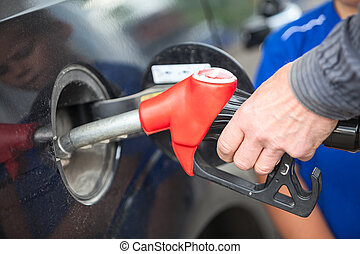 Closeup view of hand of driver inserting pumping nozzle with gasoline at the gas station