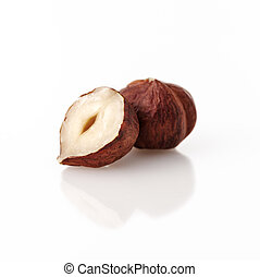 Closeup view of hazelnuts over white background.