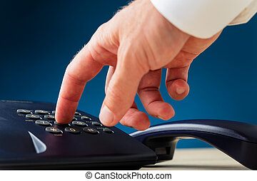 Closeup view of male hand dialing a telephone number