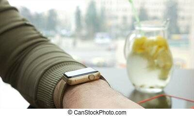 Closeup view of man checking for notifications on smartwatch while sitting at table with lemonade pitcher
