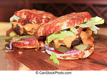 Closeup view of two messy keto burgers on a wooden board