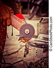 worker using a small grinder for cutting metal