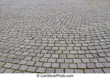 Closeup view on a cobblestone road pattern   background contrasty due to a side sunlight