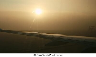 closeup view on airplane wing from window against bright sun through fog on sunrise