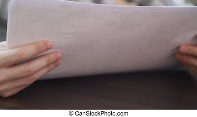 Closeup view on hands of architect with blueprints inside office.