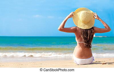 closeup, vista traseira, mulher jovem, em, biquíni, e, chapéu, com, flor, sentando praia