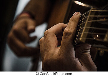 Closeup where you see the artist's hands and guitar