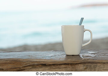 Closeup white ceramic glass of coffee on wood table with sea water and beach background