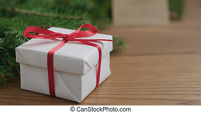 Closeup white gift box in front of spruce twigs