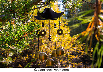 Closeup wind chimes in autumn garden. Happiness, success, power, wealth