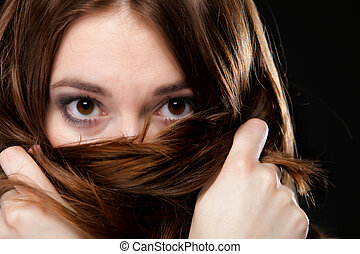 Closeup woman covers the face by long brown hairs - Close-up...