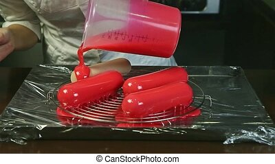 closeup woman hands pour liquid pink glaze on four frozen ...