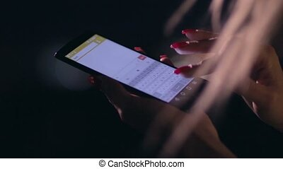 Closeup woman's hand texting on cellphone at night