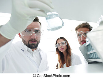 closeup.a group of scientists studying the liquid in the glass tube