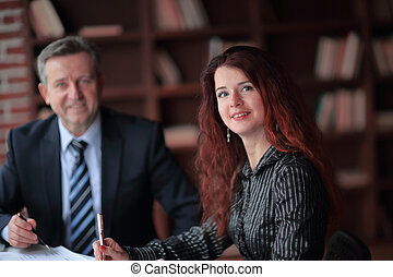 business woman and business partner sitting behind a Desk
