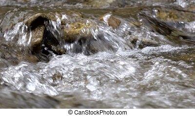 Closeups of pure stream of mountain river among stony coasts
