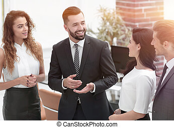 smiling business team talking, standing in office