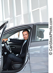 businessman sitting behind the wheel of a car, in the Parking lot at the car dealership