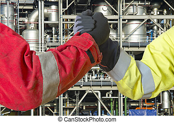 Hands of two engineers joining in closing a deal for the oil, gas and energy market as contractors, conceeding in a grant to cooperate on a joint venture.