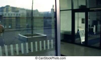 Closing automatic reflective glass door to modern business...
