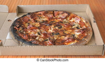 Closing cardboard box with a large pizza on the table
