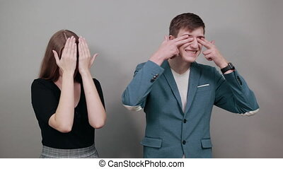 Closing face palms covers eyes visible through with hands. Young attractive couple boyfriend girlfriend two people, dressed black t-shirt, blue jacket, grey background